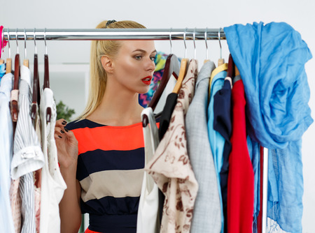 woman closet: Thoughtful beautiful blonde woman standing near wardrobe rack full of clothes and choosing dress. Shopping and consumerism or stylist concept. Nothing to wear and hard to decide concept
