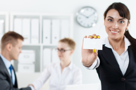 contact information: Beautiful businesswoman holding blank white calling card and showing it in camera while employees working in background. Partners contact information exchange. Introducing gesture at formal meeting Stock Photo