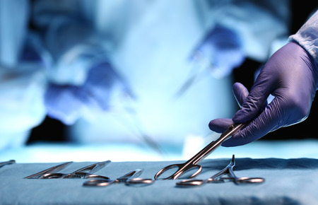 Nurse hand taking surgical instrument for group of surgeons at background operating patient in surgical theatre. Steel medical instruments ready to be used. Surgery and emergency concept