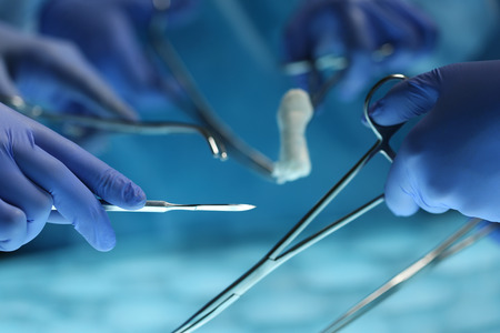 Surgeons hands holding surgical instrument while operating patient in surgical theatre. Resuscitation medicine team holding steel medical tools saving patient. Surgery and emergency concept Stock Photo