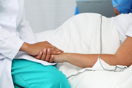 hospital care: Friendly female medicine doctor hands holding pregnant womans hand lying in bed for encouragement, empathy, cheering and support while medical examination. New life of abortion concept