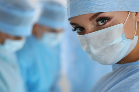 Three surgeons at work operating in surgical theatre. Resuscitation medicine team wearing protective masks saving patient. Surgery and emergency concept. Female surgeon portrait looking in camera Stock Photo