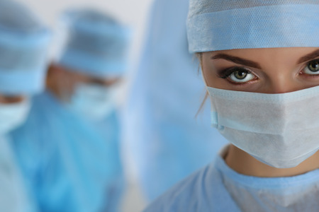 bioclean: Three surgeons at work operating in surgical theatre. Resuscitation medicine team wearing protective masks saving patient. Surgery and emergency concept. Female surgeon portrait looking in camera Stock Photo