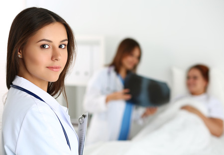 traumatology: Beautiful female medicine doctor looking in camera in front of patient lying in bed and communicating with traumatologist. Radiology or traumatology medical concept. Medical care or insurance concept