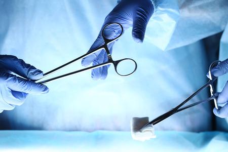 cirujano: Cirujanos tomados de la mano y que pasan instrumento quirúrgico a otro médico durante el funcionamiento del paciente. Equipo de medicina de reanimación sosteniendo herramientas médicas de acero ahorro paciente. Cirugía y el concepto de emergencia
