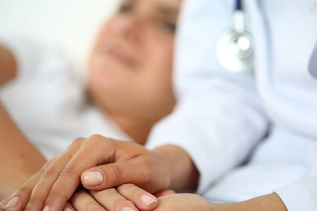 Friendly female doctor hands holding patient hand lying in bed for encouragement, empathy, cheering and support while medical examination. Bad news lessening, compassion, trust and ethics concept