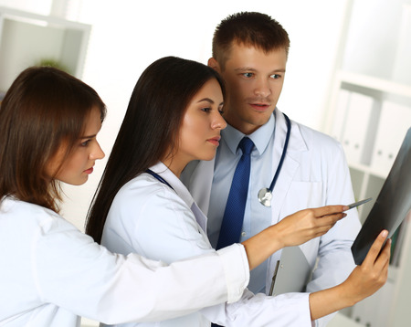 traumatology: Three medicine doctors examining x-ray photography of patient to detect problem. Professional conversation, council of physicians. Working conference. Radiologist or traumatologist medical concept Stock Photo