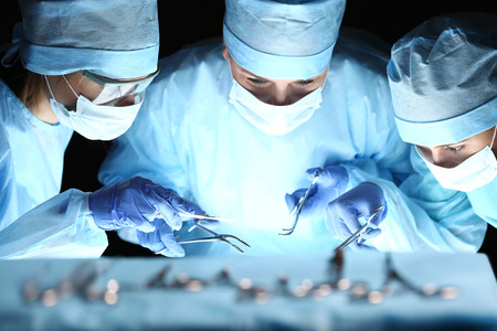 Group of surgeons at work operating in surgical theatre. Resuscitation medicine team wearing protective masks holding steel medical tools saving patient. Surgery and emergency concept Stockfoto