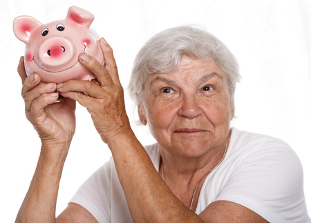 detecting: Elder woman shaking funny piggybank and listening sound of inside detecting amount. Budgeting expenses concept. Making savings and effective investment concept. Future needs deposit. Retirement wages Stock Photo