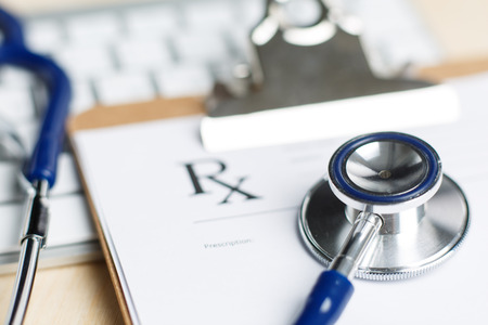 heal care: Prescription form clipped to pad lying on table with keyboard and stethoscope. Medicine or pharmacy concept. Empty medical form ready to be used