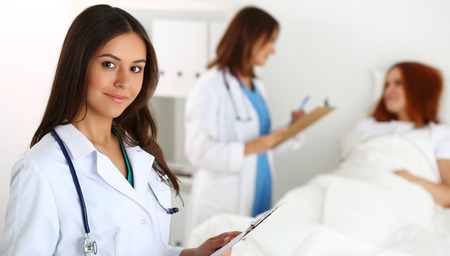patient care: Beautiful female medicine doctor looking in camera in front of patient lying in bed and communicating with therapeutist. Physician or traumatologist medical concept. Medical care or insurance concept