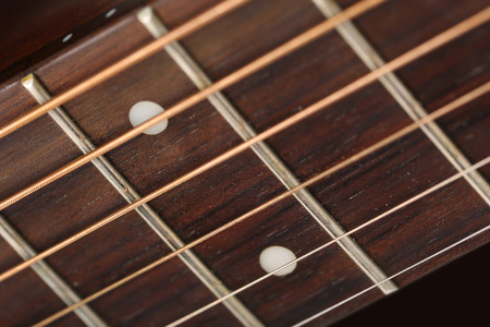 frets: Empty wooden rosewood fingerboard of classic acoustic guitar closeup. Six strings, free frets and fretboard dots. Musical instruments shop or learning school concept