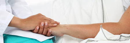 bad news: Friendly female doctor hands holding patient hand lying in bed for encouragement, empathy, cheering and support while medical examination. Bad news lessening, compassion. Letterbox view Stock Photo