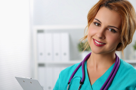 exam room: Beautiful charming friendly smiling female medicine therapeutist doctor standing in office, holding document pad and looking in camera. Medical help, physician reception or insurance concept
