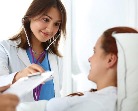 a hospital: Female medicine doctor communicating, examining and listening with stethoscope patient during ward round while nurse filling in patient medical history list. Medical care or insurance concept