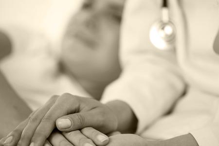 empatia: Amistosos Mujeres médico manos sosteniendo la mano paciente acostado en la cama para el estímulo, la empatía, vítores y apoyo, mientras que el examen médico. Disminución Malas noticias, la compasión, la confianza y la ética concepto Foto de archivo