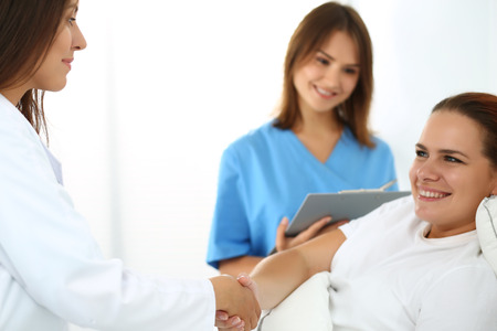 medical treatment: Female doctor shaking hands with patient lying in bed. Greeting and cheering gesture. Thankful handclasp for excellent treatment. Medical care or insurance concept. Physician ward round Stock Photo