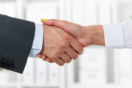 businesswoman suit: Male and female handshake in office. Businessman in suit shaking womans hand. Serious business and partnership concept. Partners made deal, sealed with handclasp. Formal greeting gesture