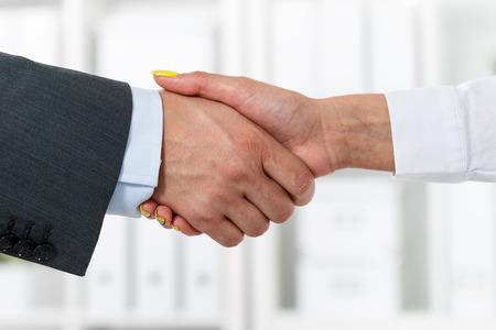 stretta di mano: Maschio e femmina stretta di mano in ufficio. Uomo d'affari in tuta stringe la mano della donna. Seria e il concetto di partenariato. Partners fatti affare, sigillato con stretta di mano. Formale gesto di saluto