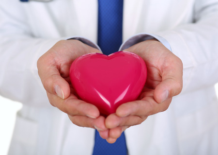 pacemaker: Male medicine doctor hands holding red toy heart in front of his chest closeup. Medical help, cardiology care, health, prophylaxis, prevention, insurance, surgery and resuscitation concept