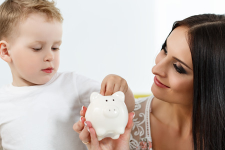 son deposit: Smiling brunette woman and little boy putting pin coins into white piggybank slot. Mother and son playing. Making family savings and effective investment concept. Future needs deposit