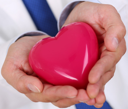 prophylaxis: Male medicine doctor hands holding and covering red toy heart closeup. Medical help, cardiology care, health, prophylaxis, prevention, insurance, surgery and resuscitation concept Stock Photo