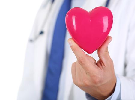 ataque al corazón: Masculino medicina médico manos sosteniendo el corazón rojo de juguete delante de su primer pecho. Ayuda médica, cuidado de la cardiología, la salud, la profilaxis, la prevención, el seguro, la cirugía y el concepto de la reanimación Foto de archivo