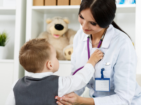 paediatrics: Family doctor examination. Little child visiting pediatrician playing with stethoscope. Beautiful female medical freckled doctor communicating with cute young patient. Paediatrics medical concept