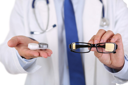 Male doctor hands giving pair of black glasses and contact lens to patient offering choice. Eyesight correction. Ophthalmology, excellent vision or optician shop concept. Laser surgery alternative