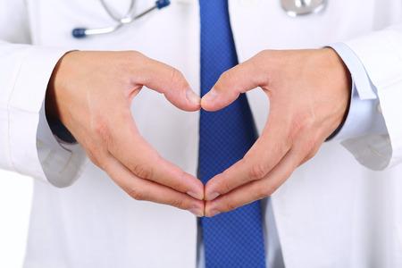 forme: Homme mains médecine médecin montrant forme de coeur agrandi. L'aide médicale, la prophylaxie ou d'un concept d'assurance. Soins de cardiologie, la santé, la protection et la prévention. Concept de la santé du coeur