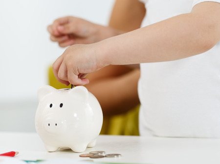 hand with money: Child hand putting pin money coins into white piggybank slot. Budgeting expenses concept. Making savings and effective investment concept. Future needs deposit. Focus on hand Stock Photo