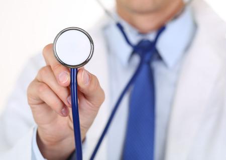 estetoscopio: Masculino medicina m�dico explotaci�n de la mano estetoscopio cabeza primer plano delante de su pecho. Ayuda m�dica o concepto de seguro. M�dico est� dispuesta a examinar paciente y ayuda. El tratamiento y la atenci�n de los pacientes concepto