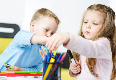 colour pencils: Children playing. Little boy and girl spending time together. Brother and sister drawing something with multicoloured pencils. Girl choosing suitable colour from bunch of pencils. Family concept
