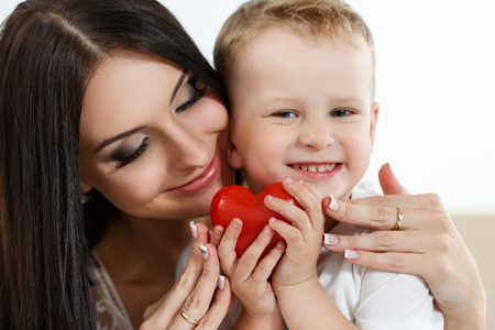 little boys: Mother and son playing. Beautiful young smiling woman hugging her child. Little boy holding heart in hands. Childhood and parenthood concept. Hand in hand. Orphanage and adoption concept