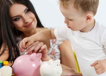 son deposit: Smiling brunette woman and little boy putting pin coins into pink piggybank slot. Mother and son playing. Making family savings and effective investment concept. Future needs deposit. Focus on hand