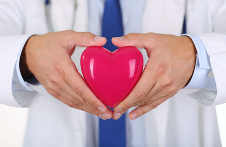 Male medicine doctor hands holding red toy heart in front of his chest closeup. Medical help, cardiology care, health, prophylaxis, prevention, insurance, surgery and resuscitation concept