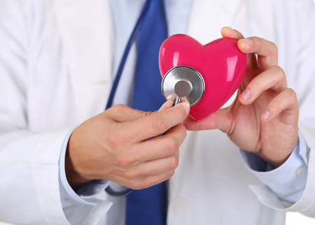 Male medicine doctor holding red heart and putting stethoscope head close to it closeup. Medical help, cardiology care, health, prophylaxis, prevention, insurance, surgery and resuscitation concept Stock Photo