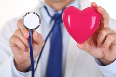 prophylaxis: Male medicine doctor holding red heart and stethoscope head in front of chest closeup. Medical help, cardiology care, health, prophylaxis, prevention, insurance, surgery and resuscitation concept