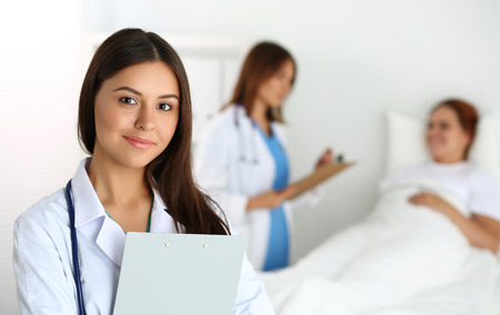 Beautiful female medicine doctor looking in camera in front of patient lying in bed and communicating with therapeutics. Stock Photo