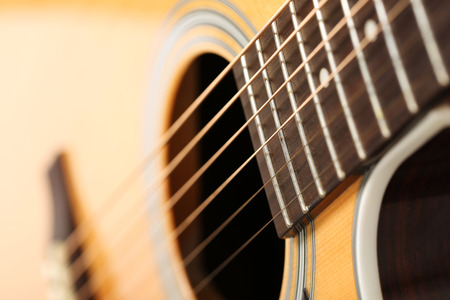 soundboard: Classic acoustic guitar at weird and unusual perspective closeup. Six strings, free frets, sound hole and soundboard. Musical instruments shop or learning school concept