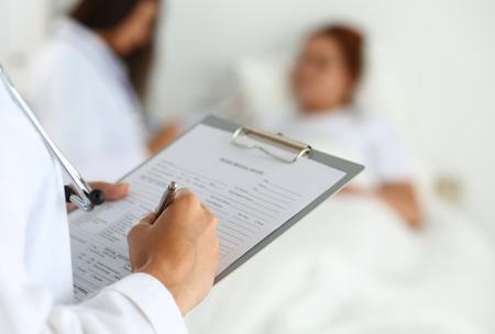 환자가 의사와 통신하는 동안 구청 라운드 동안 환자의 의료 기록 목록에 작성 여성 의학 의사. 의료 또는 보험 개념입니다. 검토하고 도움을 의사 준