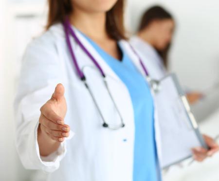 visitador medico: Mujer medicina médico que ofrece la mano para estrechar primer. Saludo y bienvenida gesto. Cura médica y pruebas anuncio concepto. Médico dispuesta a examinar paciente. Enfoque en la mano