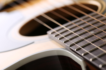 frets: Classic acoustic guitar at weird and unusual perspective closeup. Six strings, free frets, sound hole and soundboard. Musical instruments shop or learning school concept