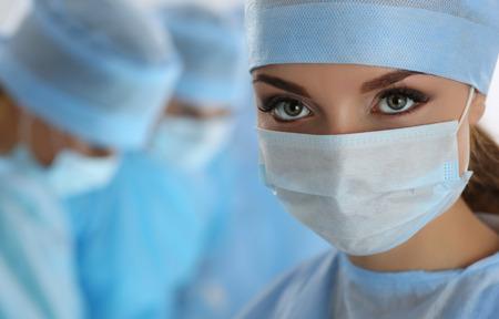 cirujano: Tres cirujanos en el trabajo que opera en quirófano.