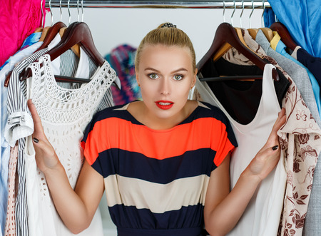 woman closet: Beautiful smiling blonde woman standing inside wardrobe rack full of clothes suffering with choice.