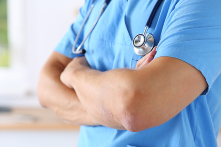 therapeutist: Male medicine therapeutist doctor hands crossed on his chest in office closeup.