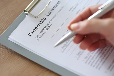clipped: Hand of businesswoman filling and signing with silver pen partnership agreement form clipped to pad closeup. Business success, contract, paperwork or lawyer concept. Focus on document