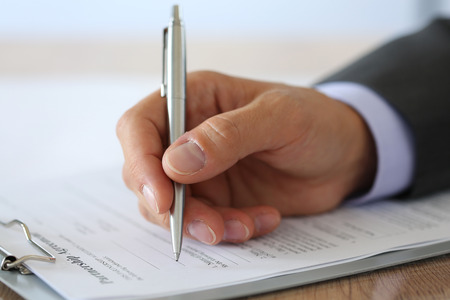 lawyer meeting: Hand of businessman in suit filling and signing with silver pen partnership agreement form clipped to pad closeup.  Stock Photo