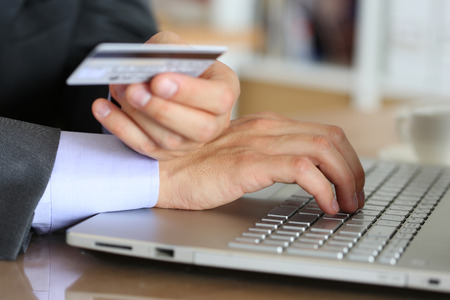 fraud: Hands of businessman in suit holding credit card and making online purchase using notebook pc.  Stock Photo
