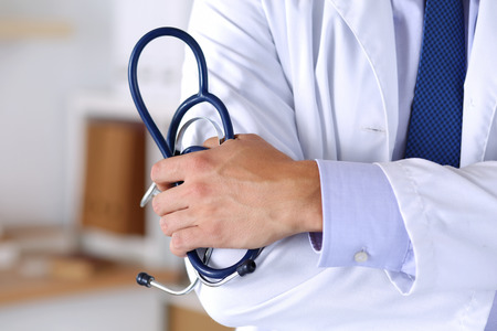 therapeutics: Male medicine therapeutics doctor hands crossed on his chest holding stethoscope in office closeup. Medical help or insurance concept. Physician is waiting for patient to examine